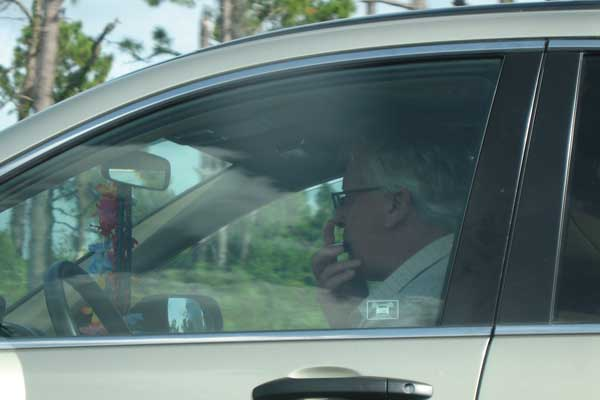 Man driving on the Interstate while playing the harmonica